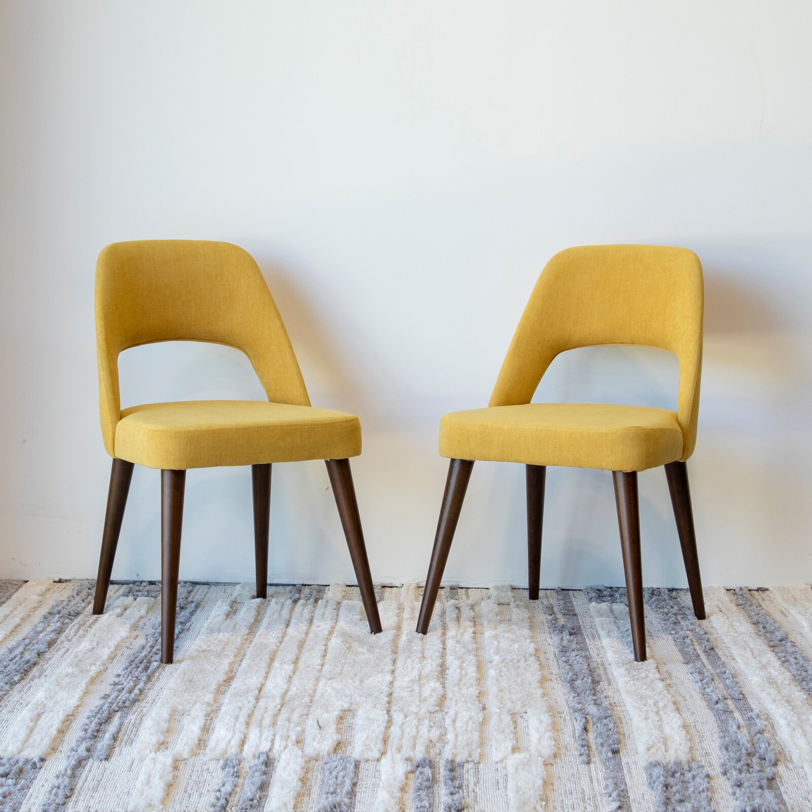 linen-upholstered-dining-chairs-bright-yellow-fabric-tapered-wood-legs-retro-dining-room-furniture-inspiration